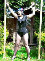 Gothic babe cuffed and bit-gagged outdoors